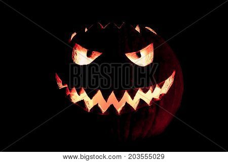 Round halloween pumpkin smile with hot burning fire eyes mouth. The big helloween symbol has a mad face glowing eyes and also a glow in its mouth and teeth. Black orange nightmare of October 31st.