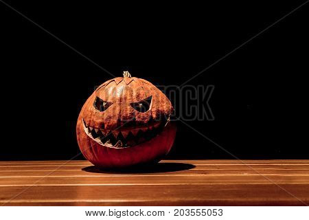 Lonely halloween pumpkin smile with black dark fire eyes mouth. Big spooky helloween symbol has darkest mad face and smiling with sharp teeth and bad look. Black orange nightmare of October 31st.