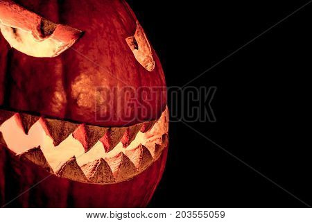 Side view halloween pumpkin smile with fire burning eyes mouth. Big spooky helloween symbol has a glowing mad face and smiling with sharp teeth and bad look. Black orange nightmare of October 31st.