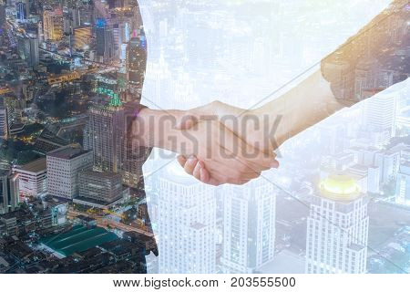 Double exposure of business handshake and business people on deal concept with city background.