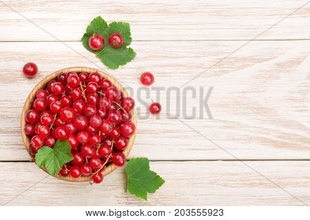 Red currant berries in a wooden bowl with leaf on the light wooden background with copy space for your text. Top view.