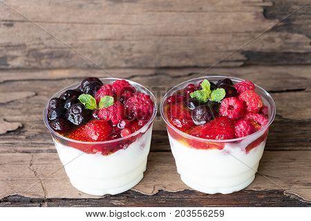 Yogurt fruit berries in the morning on old wood floor.