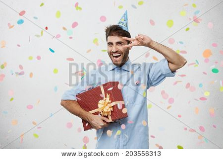 Waist Up Shot Of Euphoric And Overjoyed European Guy Wearing Shirt And Holiday Cone Hat Feeling Exci