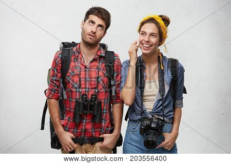 Portrait Of Young Male Explorer With Binoculars Feeling Bored While His Wife Is Chatting On Smart Ph