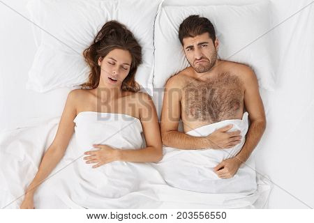 Indoor Shot Of Brunette Female Takes Nap With Husband In Comfortable Hotel. Discontent Fatigue Male