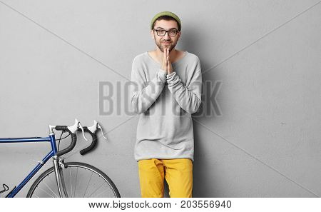 Handsome Guy With Beard, Wearing Hat, Loose Sweater And Yellow Trousers, Keeping Hands Together Havi