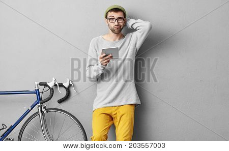 Horizontal Portrait Of Handsome Fashionable Guy Having Hesitations, Frowning His Face While Reading