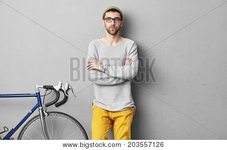 Serious Hiker With Thick Beard, Blue Eyes, Wearing Trendy Hat, Eyeglasses Keeping Hands Crossed, Sta
