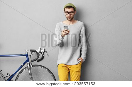 Good Looking Fashionable College Student With Stubble Relaxing With Mobile Phone, Standing At Grey W