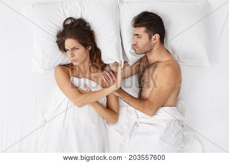 Indoor Shot Of Adult Married European Couple Having Disagreement In Bedroom. Beautiful Annoyed Woman