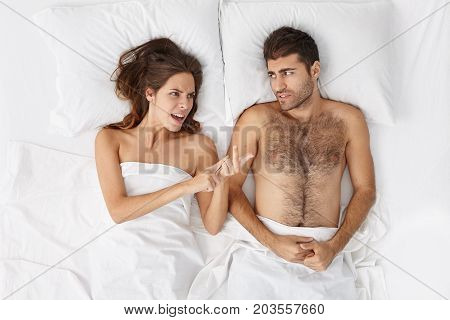 High Anle View Of Angry Irritated Young Woman Lying In Bed With Husband And Counting On Fingers All