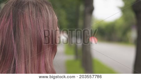 happy teen girl with purple hair standing in town side view, wide photo
