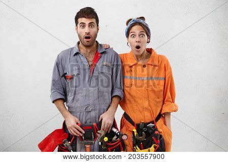 Picture Of Two Astonished Young Caucasian Repairers In Overalls Carrying Belt Kit Of Instruments Loo