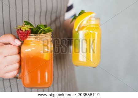 Waiter brings jars of fresh fruit cocktails in hands. Orange and strawberry cold drink with mint and ice, refreshment and satisfying thirst in hot weather, free space on right