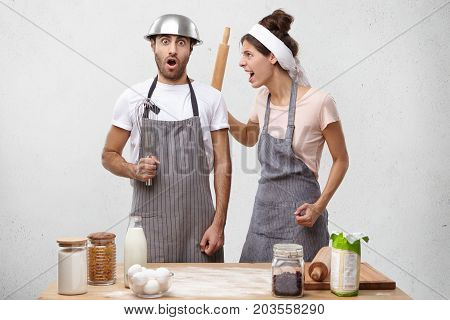 Furious Housewife Wearing Apron, Raising Her Hand With Rolling Pin, Screaming At Husband Who Forgot