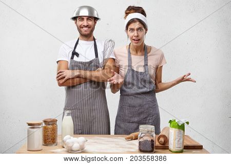 Housewife Being Annoyed With Husband Who Foolishes At Kitchen, Wears Bowl On Head, Doesn`t Want To H