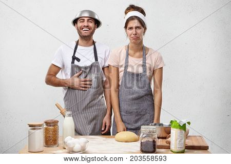 Portrait Of Talented Cookers Participate In Culinary Competiton, Cook Together As Team, Stand Near T
