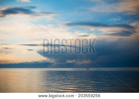 Fishermen go fishing from a boat at sunrise. Sunset on the lake, boat. Man exulted under amazing view.