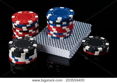 Poker chips on a deck of cards for playing poker on a black background with reflection