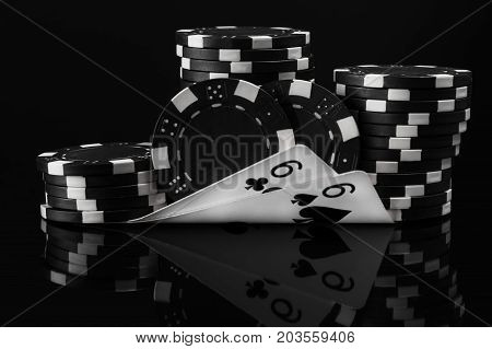 black white idea of poker chips and poker cards in poker on a black background