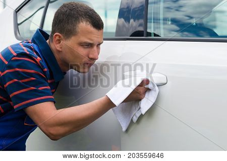 the man rubs the cloth handle of a car door and polished the door