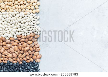 Different kinds of beans: black pinto white and chickpeas on a concrete background copy space horizontal