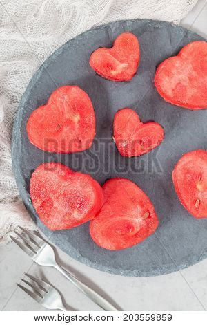 Slices of fresh seedless watermelon cut into heart shape on a slate board flat lay vertical