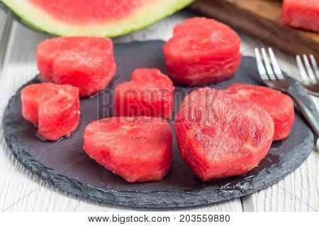 Slices of fresh seedless watermelon cut into heart shape on a slate board horizontal