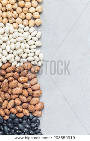 Different kinds of beans: black pinto white and chickpeas on concrete background copy space vertical