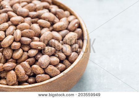 Uncooked dry pinto beans in wooden bowl copy space horizontal