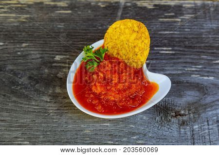 Bowl Of Adjikasalsa Placed On Top Of Corn Chips