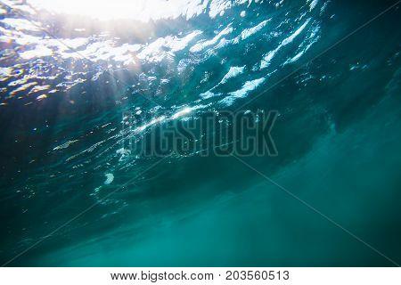 Wave underwater with sun light. Blue ocean in underwater