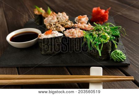 Japanese restaurant, seaweed gunkan sushi platter closeup on rustic wood background and black slate plates.. Set with chopsticks, ginger, soy, wasabi.