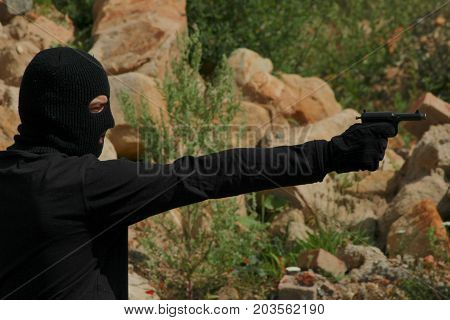 Man aggressor in black clothes with balaclava hold firearm