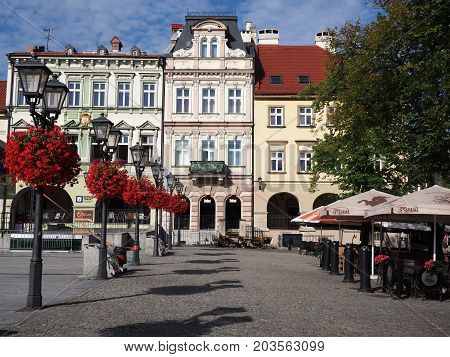 BIELSKO-BIALA, POLAND EUROPE on AUGUST 2017: Main square in historical city center with colorful old buildings, street lamps and red flowers, clear blue sky in warm sunny summer morning day.