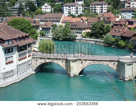 BERN BERNE, SWITZERLAND, bridge over clean alpine Aare river with clean water and cityscape landscape of historical houses on bank in swiss capital city in warm sunny summer day, EUROPE on JULY