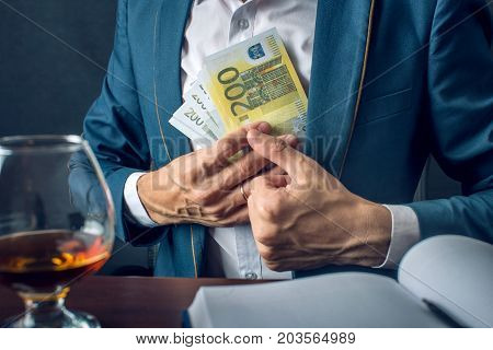 Man Businessman In Suit Puts Money In His Pocket. A Bribe In The Form Of Euro Bills. Concept Of Corr