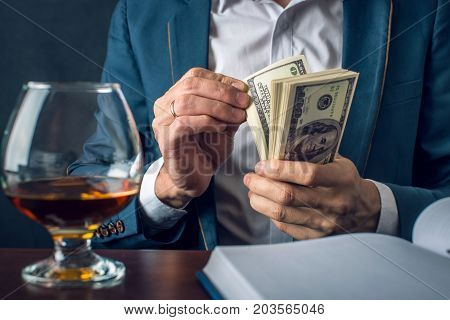 Man Businessman In Suit Holding Money In His Hands. Bribe In The Form Of Dollar Bills. Concept Of Co