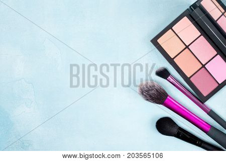 Palette of blush and brush for makeup on a blue background. view from above