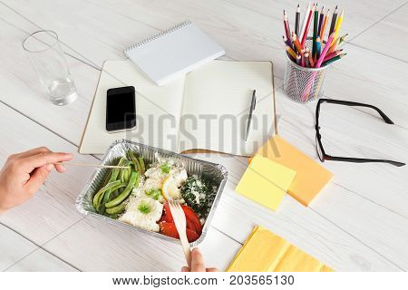 Eating healthy lunch at workplace in the office. Vegetables with parmesan plate on white wooden desk near mobile phone and open organizer. Snack at break time