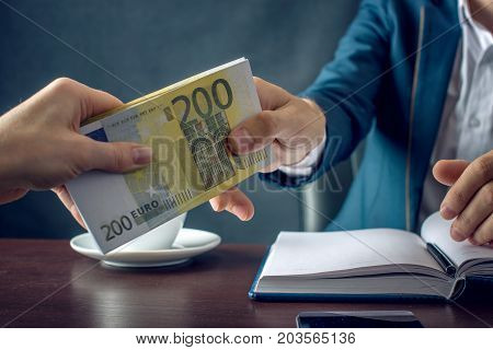 Man Businessman In Suit Takes The Money Hands. A Bribe In The Form Of Euro Bills. Concept Of Corrupt