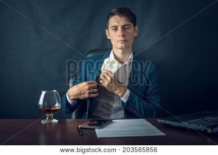 Man Businessman In Suit Puts Money In His Pocket. A Bribe In The Form Of Dollar Bills. Concept Of Co