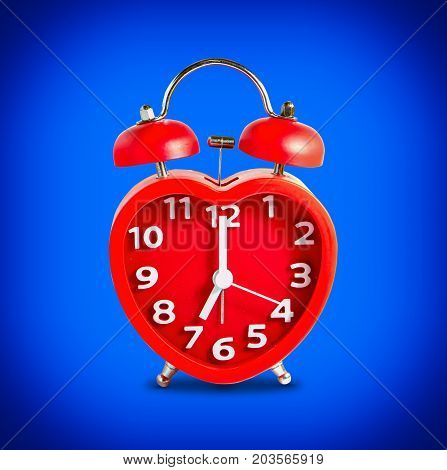 Red double bell alarm clock isolate on blue background