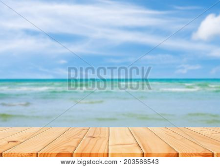 Wooden table in front of abstract blurred sea & coconut tree background. For present your products. Summer Concept