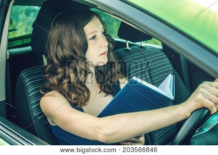 The driver woman reading a book in the car. Distracted and dangerous driving. The traffic violation. poster