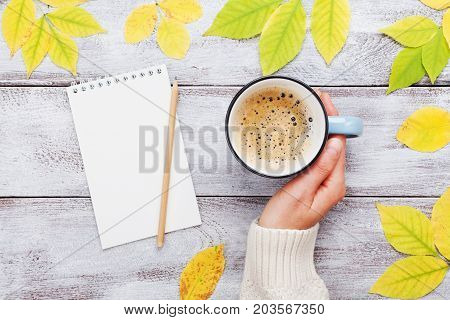 Woman hand holding cup of coffee open notebook and autumn leaves on vintage wooden table top view. Cozy breakfast. Fall bucket list. Flat lay.