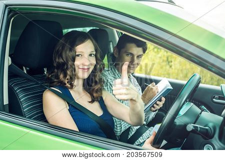 Instructor And Female Student Driving Showing Thumb Up. Woman Passed The Exam In Driving School.