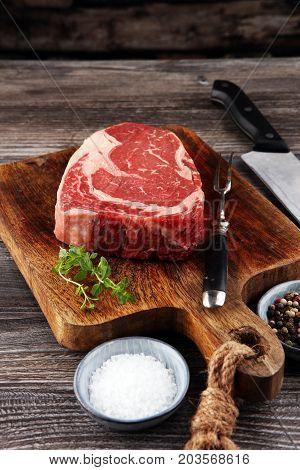 Raw Fresh Meat Ribeye Steak, Seasoning And Meat Fork On Dark Bac