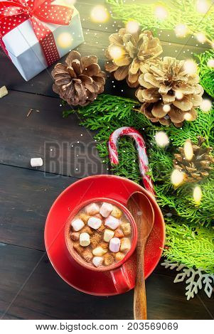 Christmas traditional hot drink cocoa in red cup fir branches and bumps cones on the dark wooden background Christmas evening Christmas card Holiday Concept Top view copy space