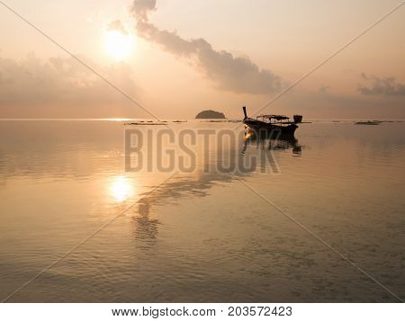 Sunrise at sea orange sky sun long tail boat and cloud reflect with sea. Peaceful and relax feeling at tropical sea.